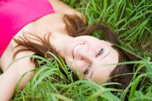 外の強い日差しの中で笑顔をカメラに向ける女性
