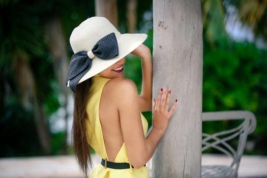 肩を出したワンピースと大きなリボン付きの帽子を身に着けた女性