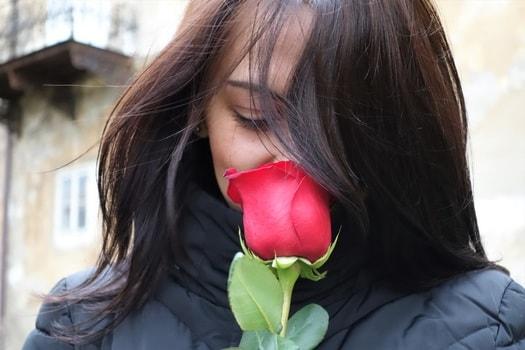赤いチューリップの匂いを嗅ぐロングヘアーの女性。赤と黒のコントラストが美しい写真。