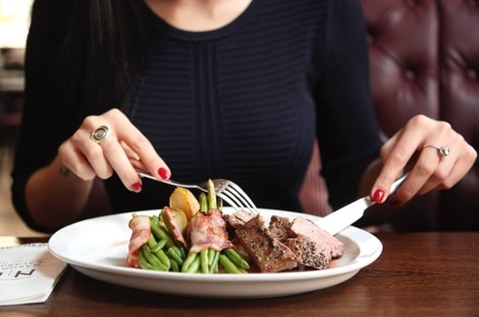 料理を食べる巨乳女性