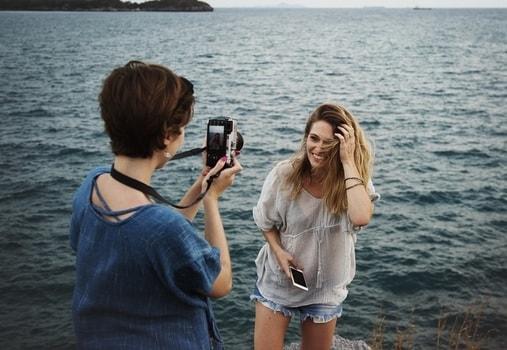 女友達に写真を撮ってもらっている女性